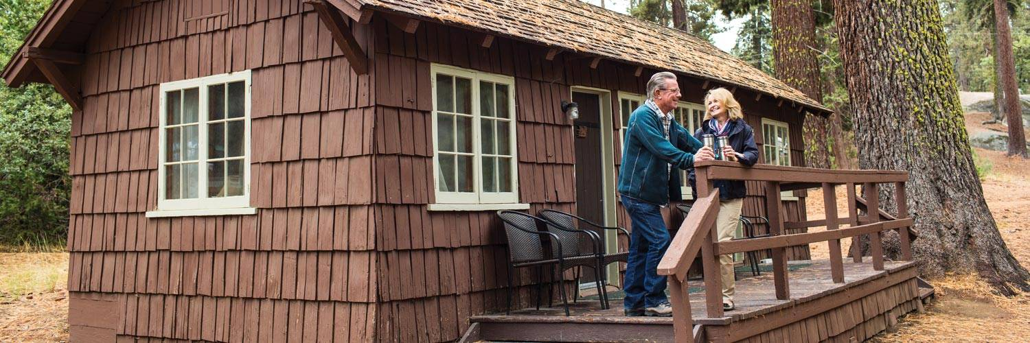 A couple talk on the deck of one of the rustic Grant Grove Cabins in Kings Canyon National Park